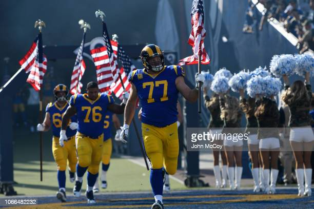 Andrew Whitworth of the Los Angeles Rams runs in with the American flag on Veterans day before playing Seattle Seahawks at Los Angeles Memorial...