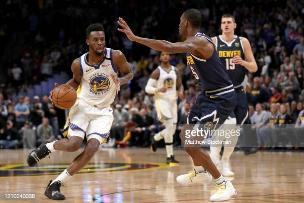 Andrew Wiggins of the Golden State Warriors drives against Will Barton III of the Denver Nuggets in the first quarter at the Pepsi Center on March...