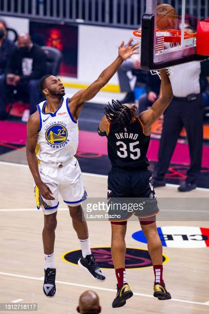 Andrew Wiggins of the Golden State Warriors reaches to block a shot attempt by Isaac Okoro of the Cleveland Cavaliers at Rocket Mortgage Fieldhouse...