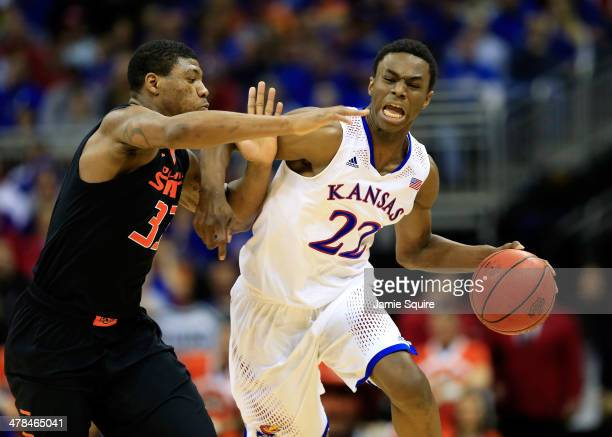Andrew Wiggins of the Kansas Jayhawks drives upcourt as Marcus Smart of the Oklahoma State Cowboys defends during the Big 12 Basketball Tournament...