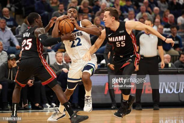Andrew Wiggins of the Minnesota Timberwolves drives to the basket against Kendrick Nunn and Duncan Robinson of the Miami Heat during the home opener...