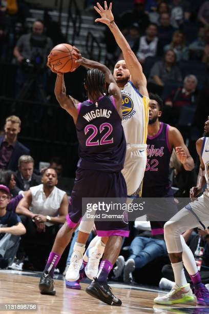 Andrew Wiggins of the Minnesota Timberwolves passes the ball around Stephen Curry of the Golden State Warriors on March 19 2019 at Target Center in...