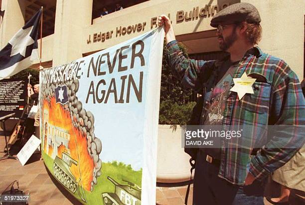 Andrew Williams of Washington DC holds up a sign depicting the scene at the Brach Davidian compound in Waco Texas during a rally at the FBI Building...