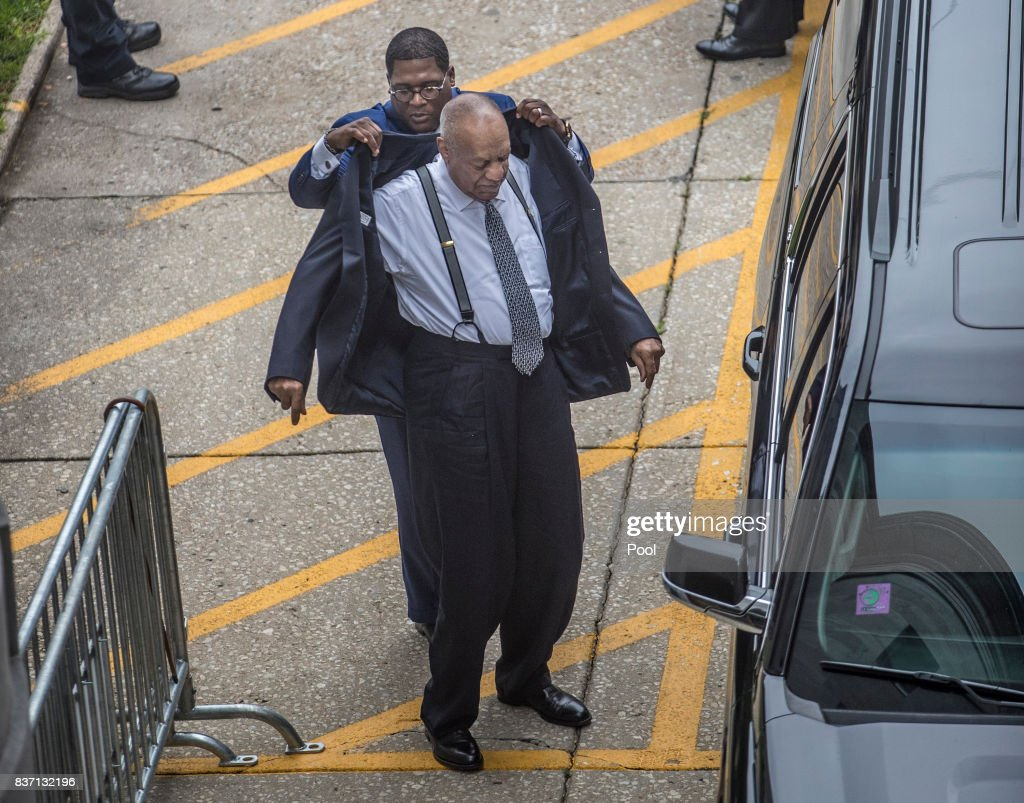 Andrew Wyatt, left, helps Bill Cosby, right, put his suit coat on after Cosby climbed out of an SUV as he arrives at Montgomery County Court on Tuesday August 22, 2017 Norristown, Pennsylvania. Bill Cosby and his new lawyers will have a hearing in Montgomery County Court about dropping his old counsel, adding his new counsel and if the jury pool will be taken out of county again.
