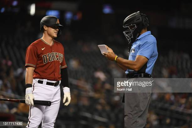 Andrew Young of the Arizona Diamondbacks checks in with home plate umpire CB Bucknor before pinch hitting for Matt Peacock against the Miami Marlins...