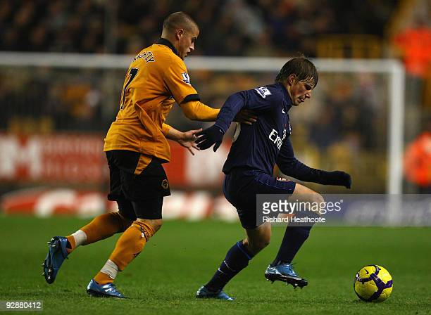 Andrey Arshavin of Arsenal is challenged by Michael Kightly of Wolverhampton Wanderers during the Barclays Premier League match between Wolverhampton...