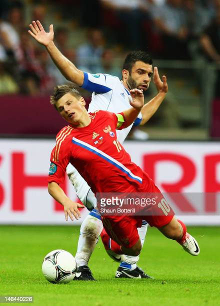 Andrey Arshavin of Russia falls under the challenge by Giorgos Tzavelas of Greece during the UEFA EURO 2012 group A match between Greece and Russia...