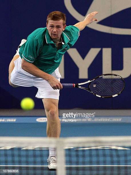 Andrey Golubev of Kazakhstan serves during their mixed doubles match against Justine Henin and Ruben Bemelmans of Belgium on day four of the Hopman...