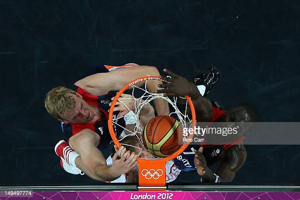 Andrey Kirilenko of Russia dunks the ball against Dan Clark and Pops MensahBonsu of Great Britain during their Men's Basketball Game on Day 2 of the...