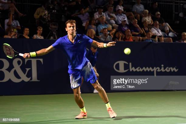 Andrey Kuznetsov of Russia returns a shot from John Isner during the fourth day of the Winston-Salem Open at Wake Forest University on August 22,...