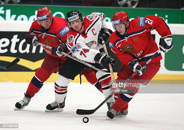 Andrey Markov and Alexander Kharitonov of Russia squeeze Dieter Kalt of Austria during the IIHF World Men's Championships preliminary round game at...