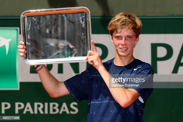 Andrey Rublev of Russia poses with the trophy after his victory in the boys' singles final match against Jaume Antoni Munar Clar of Spain on day...