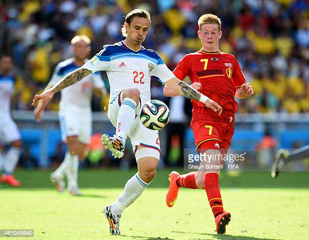 Andrey Yeshchenko of Russia and Kevin De Bruyne of Belgium compete for the ball during the 2014 FIFA World Cup Brazil Group H match between Belgium...