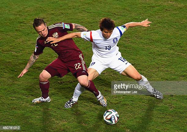 Andrey Yeshchenko of Russia competes for the ball with Koo JaCheol of South Korea during the 2014 FIFA World Cup Brazil Group H match between Russia...