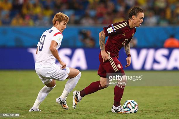 Andrey Yeshchenko of Russia controls the ball against Son HeungMin of South Korea during the 2014 FIFA World Cup Brazil Group H match between Russia...