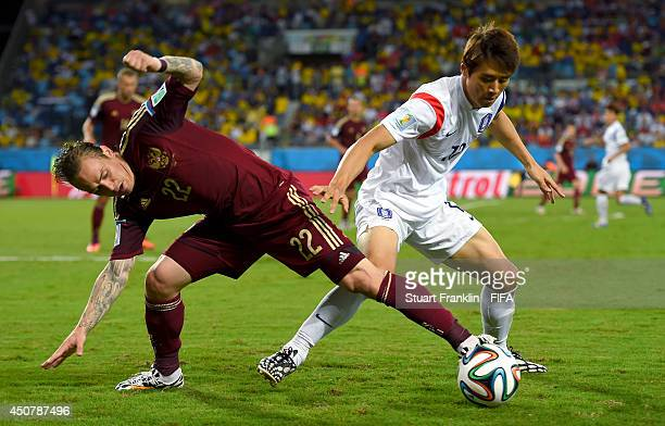 Andrey Yeshchenko of Russia vies with Koo JaCheol of South Korea of South Korea of South Korea during the 2014 FIFA World Cup Brazil Group H match...