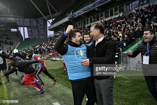 Andrezieux' French coach Jean Noel Cabezas celebrates with a player after winning the French Cup last-64 football match between Andrezieux-Boutheon...