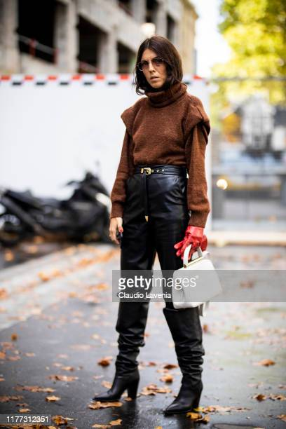 Andria Aletrari wearing a brown sweater black leather pants white bag and black boots is seen outside the Faith Connexion show during Paris Fashion...