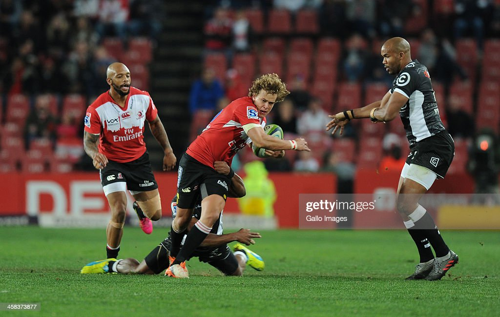 Andries Coetzee of Lions is tackled by Sipho Sithole and JP Pietersen of Sharks during the Super Rugby match between Emirates Lions and Cell C Sharks at Emirates Airline Park on July 02, 2016 in Johannesburg, South Africa.