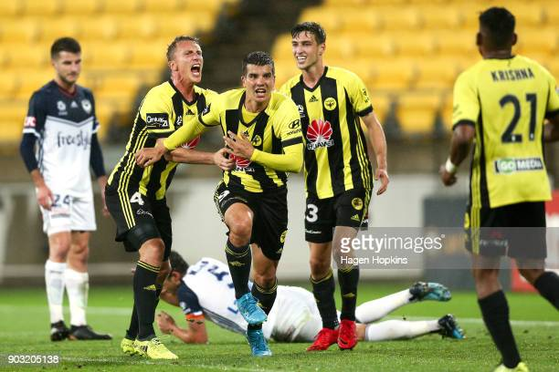 Andrija Kaludjerovic Goran Paracki and Matthew Ridenton celebrate an own goal by Mark Milligan of the Victory during the round 15 ALeague match...