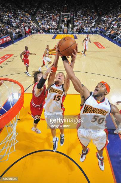 Andris Biedrins and Corey Maggette of the Golden State Warriors go after a rebound against Andres Nocioni of the Chicago Bulls during the game on...