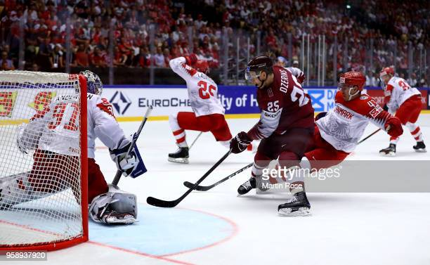 Andris Dzerins of Latvia and Nichlas Hardt of Denmark battle for the puck during the 2018 IIHF Ice Hockey World Championship Group B game between...