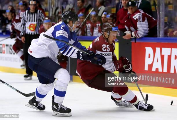 Andris Dzerins of Latvia and Ville Pokka of Finland battle for the puck during the 2018 IIHF Ice Hockey World Championship group stage game between...