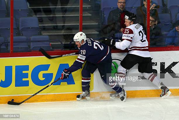 Andris Dzernis of Latvia and Ryan Carter of USA battle for the puck during the IIHF World Championship group H match between Latvia and USA at...