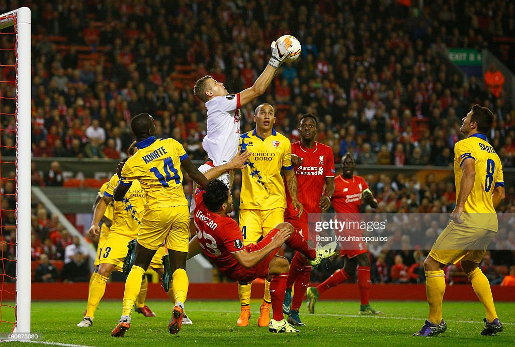 Andris Vanins of FC Sion makes a save as Emre Can of Liverpool goes to ground during the UEFA Europa League group B match between Liverpool FC and FC Sion at Anfield on October 1, 2015 in Liverpool, United Kingdom.