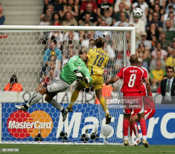 Andriy Voronin of Ukraine challenges Tunisia goalkeeper Ali Boumnijel