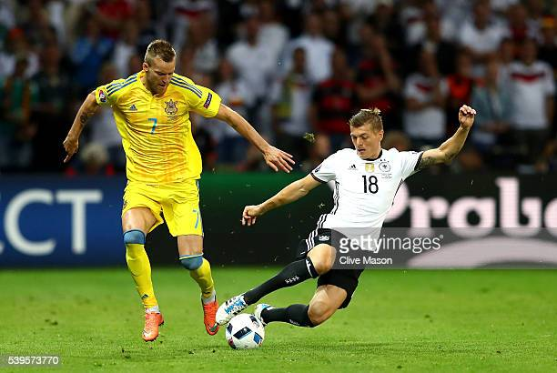 Andriy Yarmolenko of Ukraine and Toni Kroos of Germany compete for the ball during the UEFA EURO 2016 Group C match between Germany and Ukraine at...