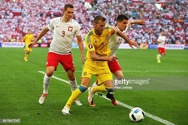 Andriy Yarmolenko of Ukraine is tackled by Artur Jedrzejczyk of Poland and Bartosz Kapustka of Poland during the UEFA EURO 2016 Group C match between...