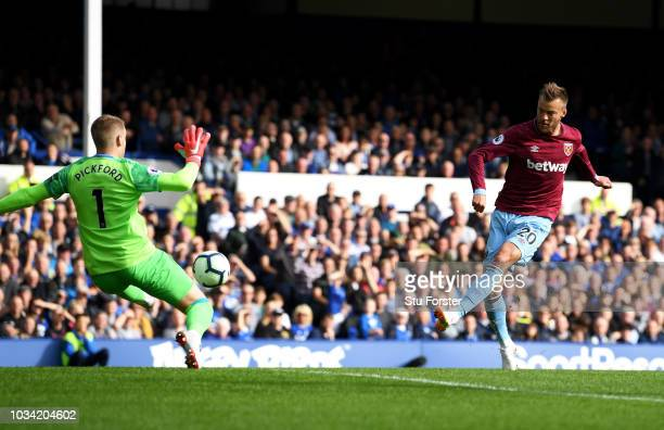 Andriy Yarmolenko of West Ham United scores his team's first goal past Jordan Pickford of Everton during the Premier League match between Everton FC...