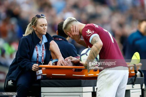 Andriy Yarmolenko of West Ham United speaks with Marko Arnautovic of West Ham United as he is taken off injured during the Premier League match...