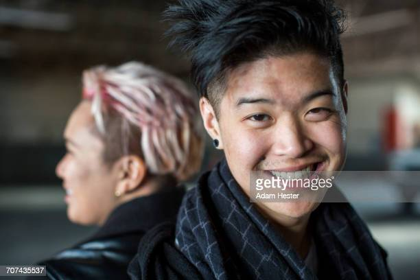 androgynous asian man and woman back to back - gender fluid stock photos and pictures