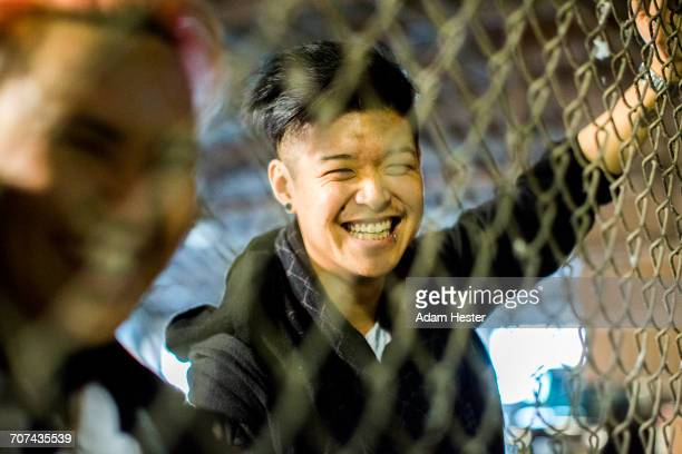 Androgynous Asian man and woman leaning on fence