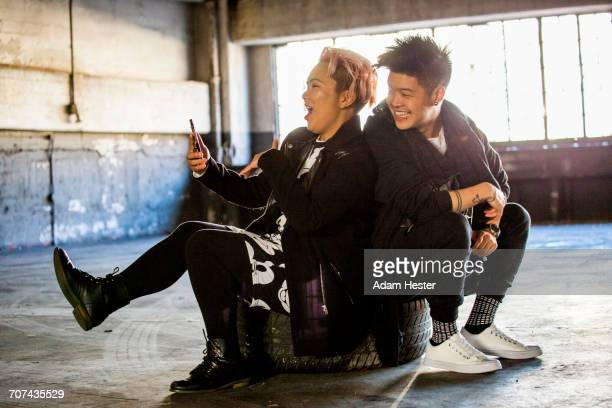 androgynous asian man and woman posing for cell phone selfie - transgender man stock photos and pictures