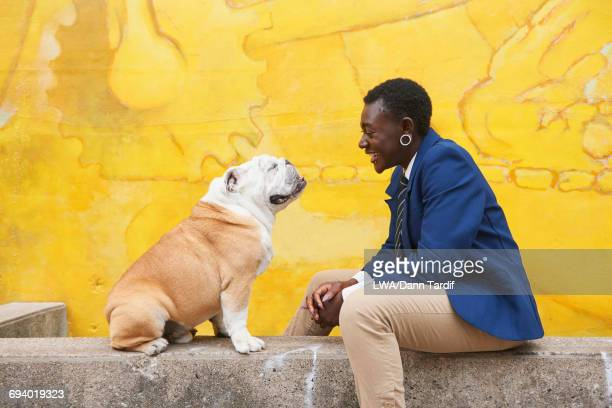 Androgynous Black woman sitting with dog near mural