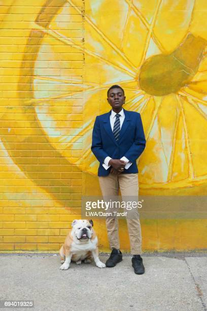 Androgynous Black woman with dog leaning on mural