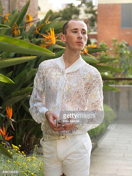 androgynous man with nail art holding sunglasses