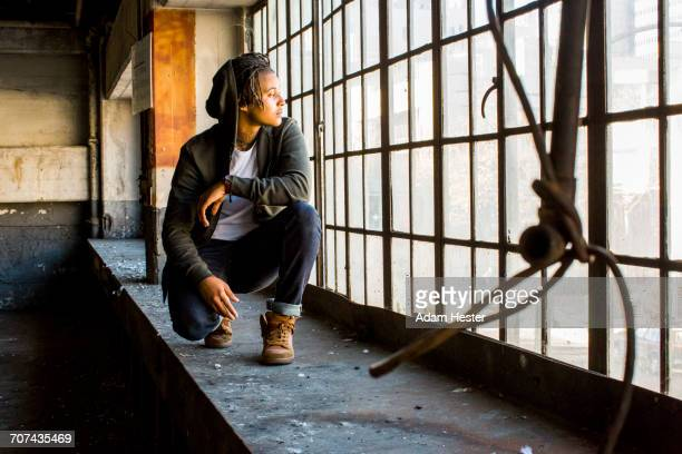 androgynous mixed race woman crouching near window - gender fluid stock photos and pictures