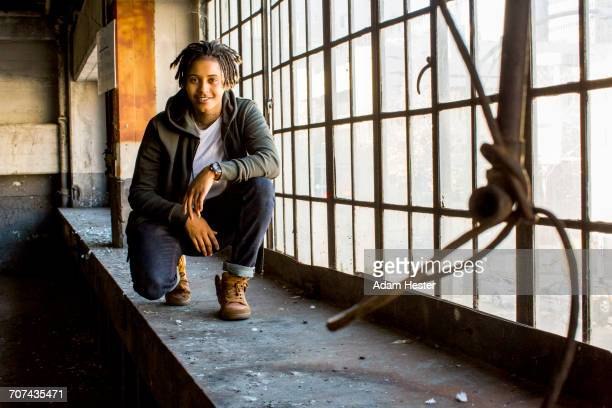 androgynous mixed race woman smiling near window - black transgender stock pictures, royalty-free photos & images