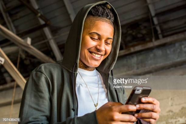androgynous mixed race woman texting on cell phone - black transgender stock pictures, royalty-free photos & images
