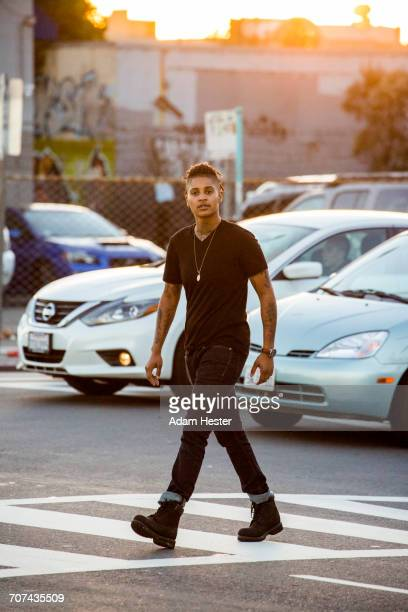 androgynous mixed race woman walking in urban crosswalk - black transgender stock pictures, royalty-free photos & images