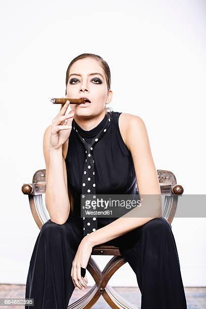 Androgynous woman smoking a cigar