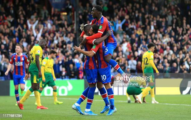Andros Townsend of Crystal Palace celebrates with teammates Wilfried Zaha and Jeffrey Schlupp after scoring his team's second goal during the Premier...