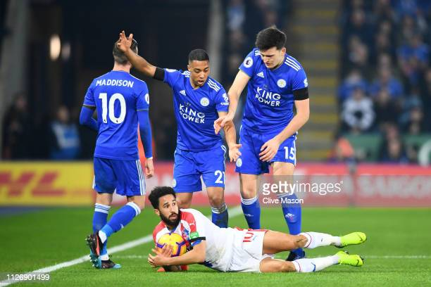 Andros Townsend of Crystal Palace reacts on the ground as Youri Tielemans and Harry Maguire of Leicester City look on during the Premier League match...