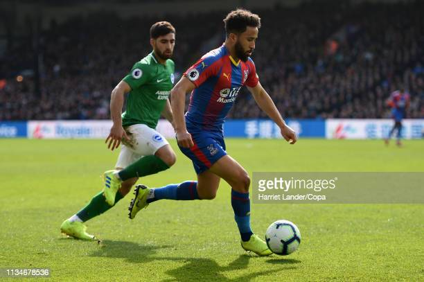 Andros Townsend of Crystal Palace runs with the ball under pressure from Alireza Jahanbakhsh of Brighton Hove Albion during the Premier League match...