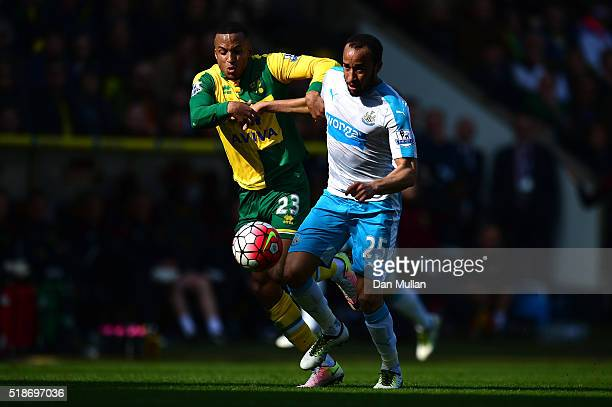 Andros Townsend of Newcastle United and Martin Olsson of Norwich City compete for the ball during the Barclays Premier League match between Norwich...