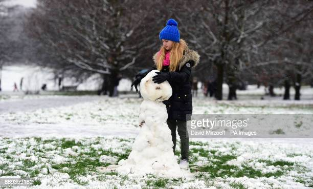 Andrra Pallaska makes a snowman on Primrose Hill in London as heavy snowfall across parts of the UK is causing widespread disruption closing roads...